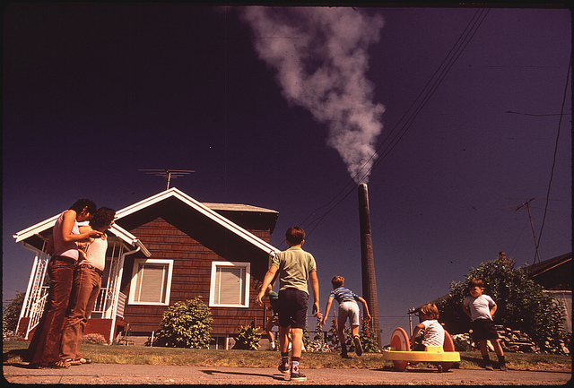 Children Play in Yard of Ruston Home, While Tacoma Smelter Stack Showers Area with Arsenic and Lead Residue, 08/1972.