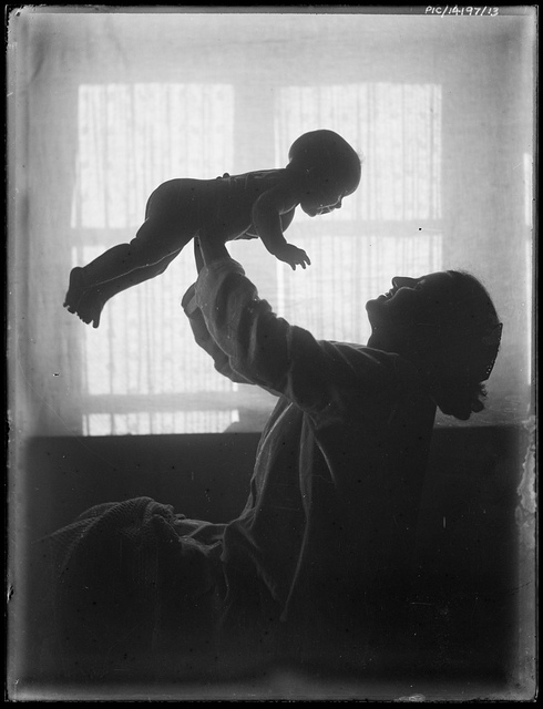Portrait of Antoinette Hurley holding her daughter Yvonne in the air, 1921?